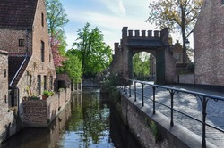 View over water of the Minnewater in Brugge, Belgium with historic buildings and entrance gate to the Princely Beguinage Ten Wijngaerde (Begijnhof Brugge)