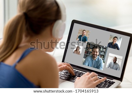 View over woman shoulder resting at home using computer, pc screen view diverse girls and guys chatting by video call enjoy distant communication. E-dating services modern tech for fun or work concept