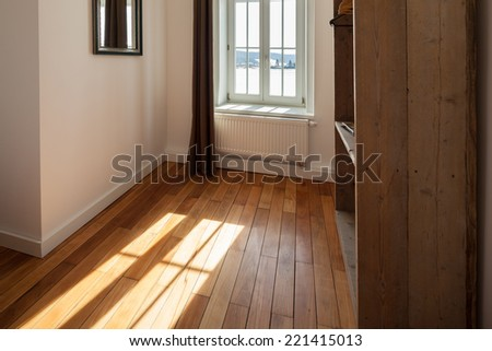 View past a shelving unit of sunlight shining onto a wooden parquet floor through a curtained window