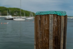View past old wooden pier to a sailboat harbor boats anchored on coastline during summer time. Beautiful exterior