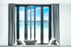view seascape beautiful tropical beach and blue sky sea and sky, thailand  from black Aluminum door with glass frame and wall in luxury resort