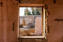 View through a broken window of ruined buildings and courtyard in Al Jazirah Al Hamra haunted town in Ras Al Khaimah, United Arab Emirates.