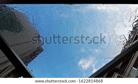 View through a glass table to the sky after it rained. An abstract perspective