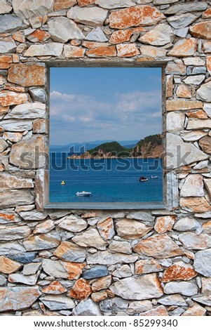 View through a stone wall window to the sea and coast