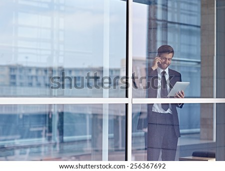 View through a window of a corporate executive talking on his phone and looking at a digital tablet stock photo