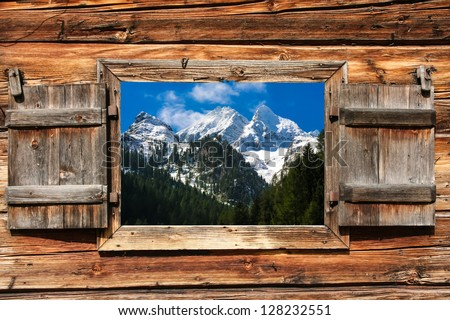 View through a wooden window on a mountain panorama with forest in foreground