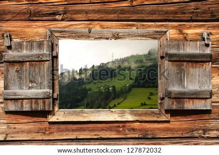 view through a wooden window on an alpine landscape