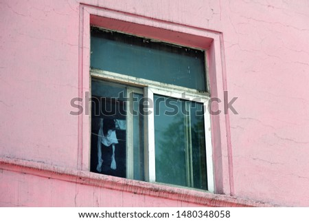 View through an open window inside a flat in a typical apartment house on the outskirts of Pyongyang. North Korea. Inside a room the clothes are dried on a rope.