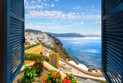 View through an open window of the Aegean Sea, caldera and town of Oia and Thira on the island of Santorini Greece.