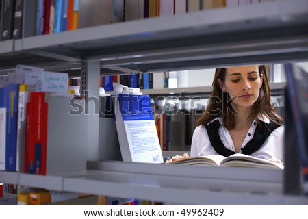 View through bookshelf at attractive student standing in between bookshelves in modern university library reading a book.