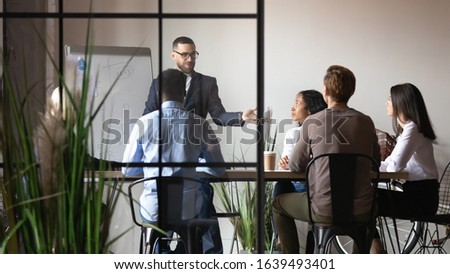 View through glass wall businesspeople brainstorming at board room staff listen executive manager defines vision goals of department, meeting led by ceo discussing strategy, new project, share ideas ストックフォト ©