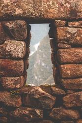 View through Inca window in Machu Picchu, Peru, South America. Archaeological site. April, 2018.