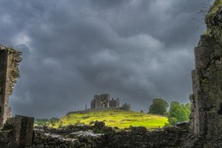 View through old ruins of Hore Abbey walls on Rock of Cashel castle with dark dramatic storm sky in the background, County Tipperary, Ireland