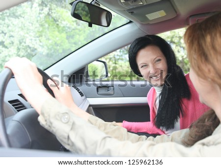 View through past the female driver to an attractive woman passenger in a motor car with focus to the passenger