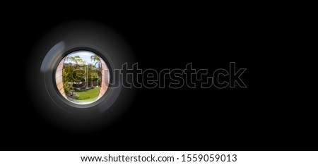 View through peephole in door looking out to entry security surveillance concept solid black background ストックフォト ©