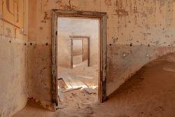 view through ruined doorways in abandoned house in Kolmanskop town, Namibia
