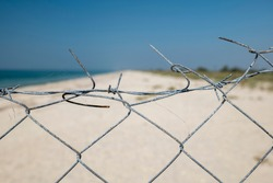 View through the barbed wire to the beach and the sea. Natural reserve. no entry