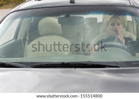 View through the front windscreen of a female driver drinking alcohol from a bottle in the car while driving along the road