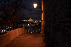 view through the old illuminated stone wall from the 17th and the light of street lighting and in the background the illuminated Prague Castle and the Church of St. Vitus, clouds at night
