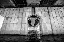 View through the pillars of the bridge. The left bank of the Dnieper in the city of Kiev. Under the bridge. Black and white photo