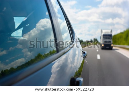 View through the rear mirror on the approaching truck on the highway. Beautiful reflections of the clouds in the windows. Shallow depth of field.