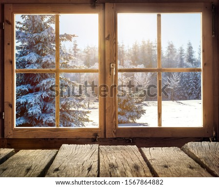 Photo of  View through the window of a cottage into a snow-covered winter forest