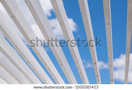 View through the wooden roof beams to the bright blue sky. Beams #1050585413