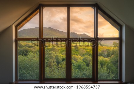View through the wooden window on beautiful, dramatic sunrise over Carrauntoohil mountain and MacGillycuddys Reeks mountains, Ring of Kerry, Ireland Stok fotoğraf ©