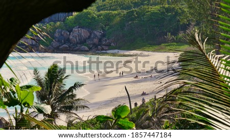 View through vegetation with tourists sunbathing on beautiful tropical beach Grand Anse in the south of La Digue island, Seychelles. Focus on beach. Photo stock ©