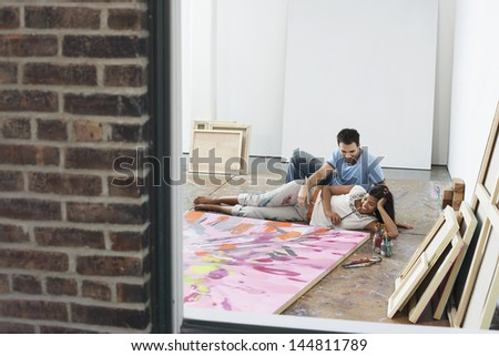 view through window of a couple reclining by painting on floor in studio
