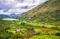 View to a mountain lake and houses in Snowdonia National Park in North Wales of the United Kingdom. Snowdonia is a mountain range and a region in North of Wales.