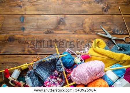 view to a wooden table with lots of balls of wool, knitting needles and other tools.  Place for text