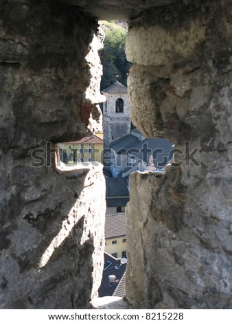 view to bellinzona town through the ancient arrow loop stock photo