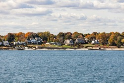 view to coast of New London to shelter island hights on a sunny day with old traditional wooden houses at the beach