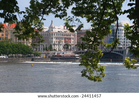 View to Dancing House, old bridge, river Vltava with ships. Big dark branch with green leaves at highlight.