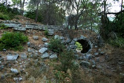 View to destroyed wall with arc exit from Theatre (theater). The Ruins Of The Ancient City Of Olympos (Cirali, Antalya region, Turkey).