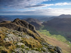 View to Loft Crag from Pike of Stickle overlooking the Great Langdale valley with Blea Tarn nestled in the fells and Windermere lake in the background, Langdale Pikes, Lake District, UK