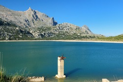 View To Mount Puig Major At Green Shimmering Lake Cuber In The Tramuntana Mountains On Balearic Island Mallorca On A Sunny Winter Day With A Clear Blue Sky