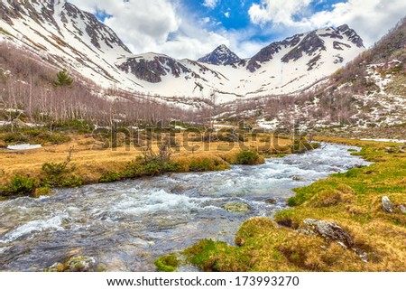 View to snow on Caucasus mountains over clear water stream near Arkhyz, Karachay-Cherkessia, Russia