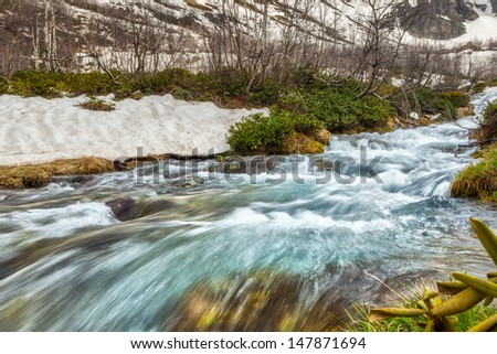 View to snow on Caucasus mountains over motion blurred stream near Arkhyz, Karachay-Cherkessia, Russia