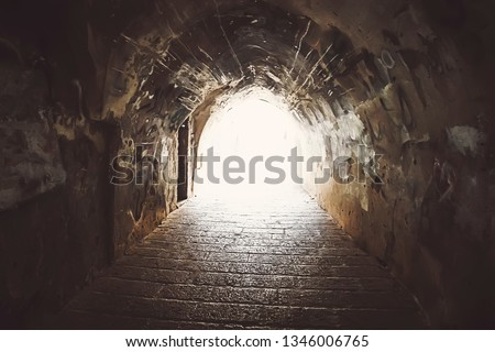 View to some old passageway with stone walls of archeway, old pavement and bright light at the end of the tunnel. The gallery leading off them for tomb. Ancient city underground tunnel. Archwise.