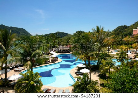 View to swimming pool and houses of tropical resort.