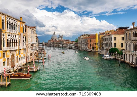 View to the Basilica di Santa Maria della Salute and Canale Grande in Venice, Italy, during a cloudy summer day #715309408