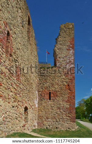 View to the red bricks ruins of Bauska Castle (Latvian Bauskas pils, German Schloss Bauske) former residence of the Duke of Courland, seat of the Livonian order, with the flag of Latvia on top
