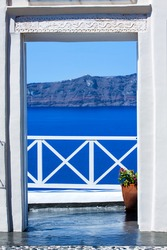 View to the sea and Volcano through a door, from Fira the capital of Santorini island in Greece