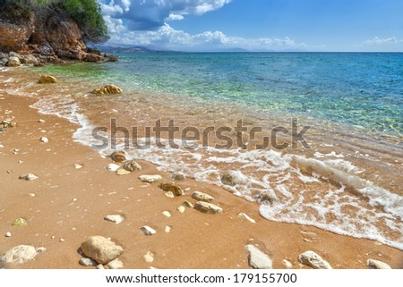 View to tide wave over pebbles and rocks on the sand under transparent water at Ionian sea floor under bright sunlight near Ipsos, Corfu, Greece