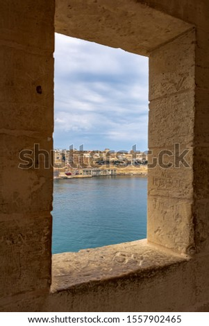View to Valletta Waterfront from the window of The Gardjola in Senglea, Malta. The Gardjola is a stone vedette at Senglea Bastion point. It was used to serve as a lookout post to guard the harbour. Stock fotó ©