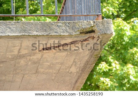 View up under a balcony of elder building. The concrete has cracks, and the carrying steel beam is attacked by rust.
