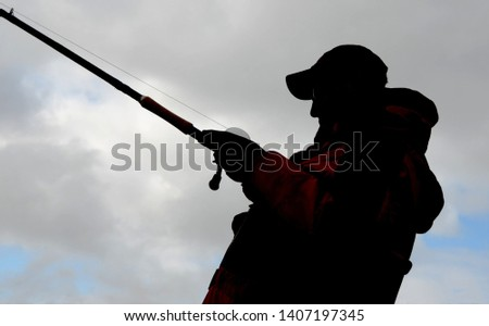 View upwards at a muskie angler in a baseball cap silhouetted against a bright partly cloudy sky with a musky fishing rod and reel combo fishing #1407197345