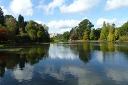 View with beautiful mirror reflection over still lake at Sheffield Park Garden in East Sussex, England, United Kingdom.